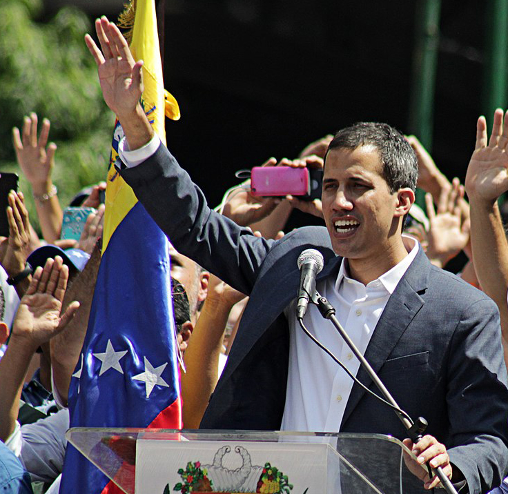 Juan Guaidó addresses a February 2019 protest in Caracas. The photo show a man in front of a microphone, raising his hand. A crowd of people behind him also have their hands raised.
