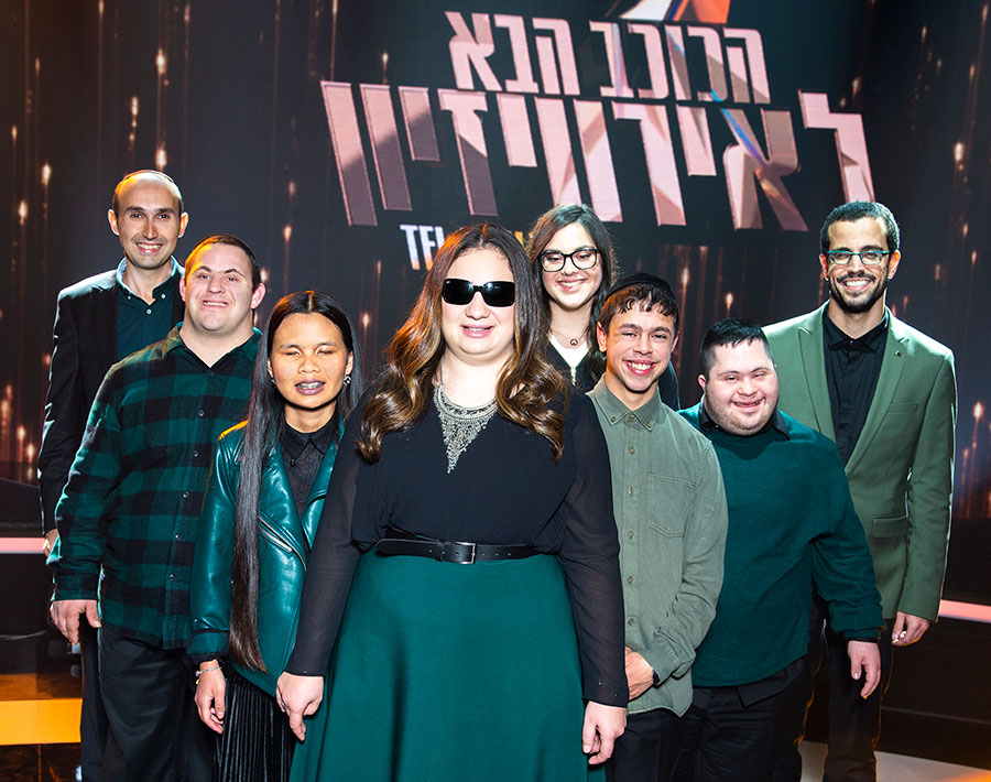 Image shows a group of eight disabled young adults posing in front a the Hebrew-language Eurovision sign.