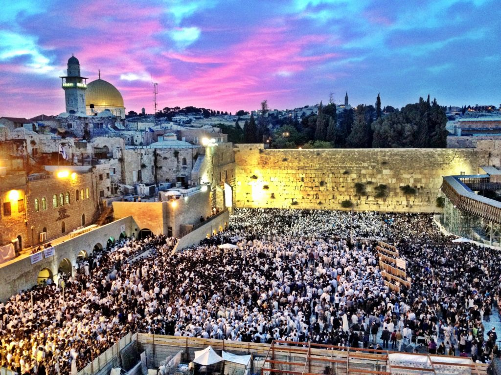 Western Wall (the Kotel) in Jerusalem on the holiday of Shavuot. The plaza is filled with worshipers.