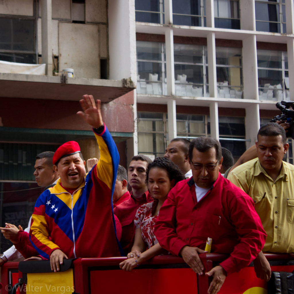 Hugo Chavez, in track suit that uses the colors and shapes of the flag of Venezuela and a military beret, waves to a crowd.