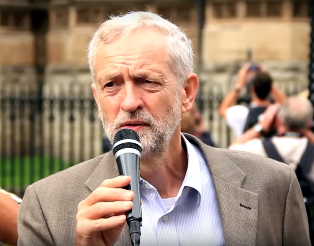 Jeremy Corbyn. Image shows a man with white hair and a beard speaking into a microphone.