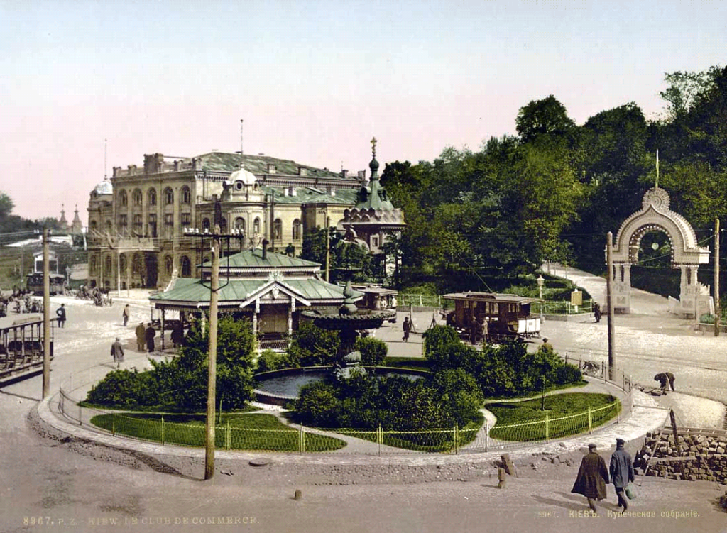 Colorized photo of an ornate building. Traffic circle (roundabout) in the foreground.