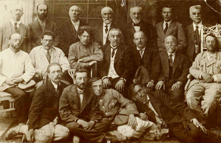 Sepia toned photograph shows 17 men sitting and standing in three rows.