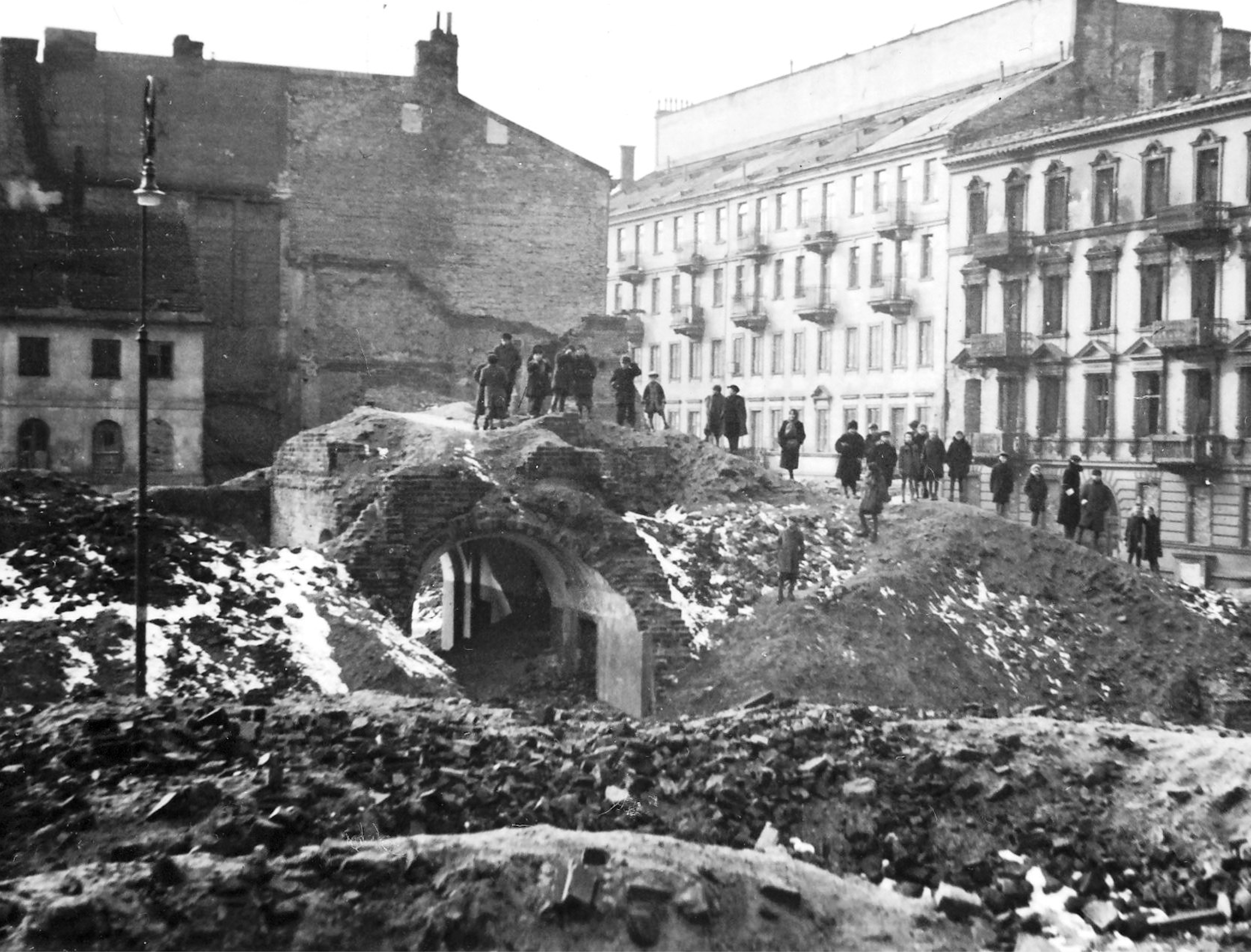 Archival black and white photo of people standing atop massive piles of rubble, all that is left of the Warsaw Ghetto.