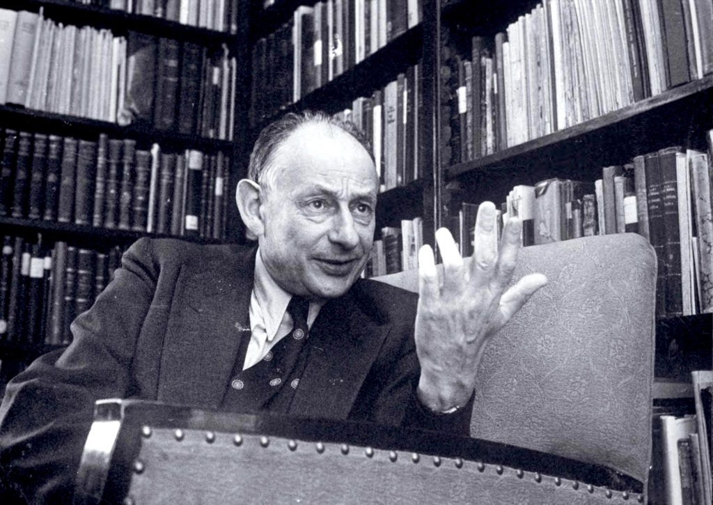 Black and white image of a blading man wearing a suit gesturing while in conversation. Behind him are bookshelves filled with books.