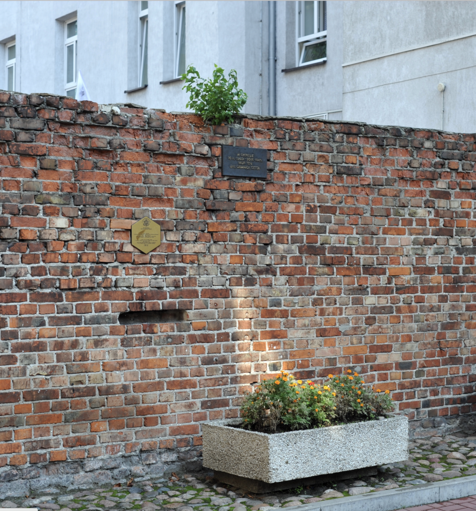 Red-brick remnant of the Warsaw Ghetto wall. A small brass plaque explains its meaning. A colorful flowerbox sits in front of the memorial.