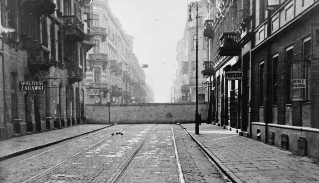 Photo of intact Warsaw ghetto wall, running perpendicular to the street.