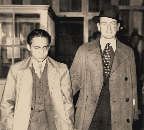 Herschel Grynszpan being led by another man after his arrest, November 7, 1938. (Private Collection/Alamy.)