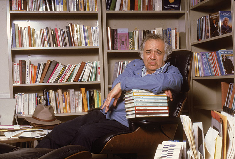Harold Bloom resting on a stack of his Chelsea House books, January 1985. (Photo by Bernard Gotfryd/ Getty Images.)