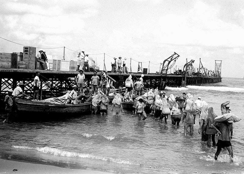 Port workers unloading sacks of cement near the breakwater at the Tel Aviv port, August 1, 1936. 