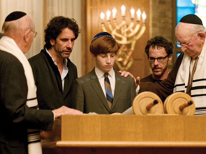 Aaron Wolff, center, surrounded by directors, Joel Coen, left, and Ethan Coen, right, on the set of  A Serious Man, 2009. (Wilson Webb/©Focus Features/Courtesy Everett Collection.)